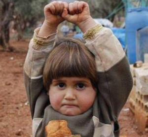 Bimba siriana che laza le mani di fronte alla telecamera del fotografo, scambiato per una canna di fucile